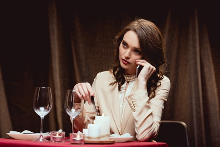 beautiful woman sitting at table and talking on smartphone in restaurant
