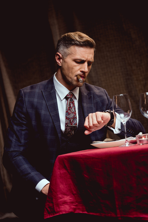 dissatisfied handsome man in suit sitting at table, smoking cigar and looking at watch in restaurant Reklamní fotografie