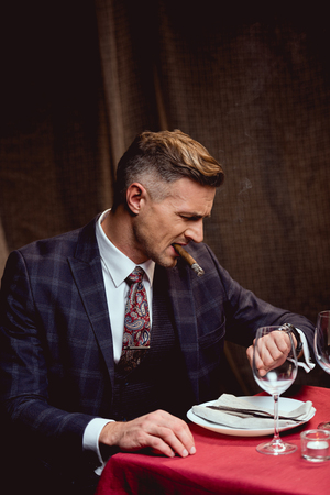 dissatisfied handsome man in suit sitting at table, smoking cigar and looking at watch in restaurant Stockfoto