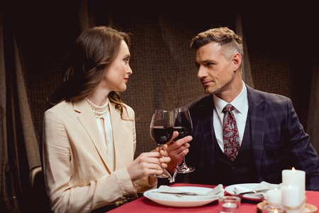 couple sitting at table and clinking glasses of red wine during romantic date in restaurant