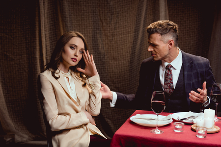 couple quarreling while having romantic date in restaurant