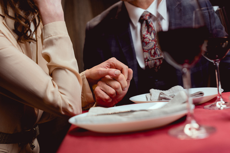 partial view of couple holding hands while having romantic date in restaurant Stok Fotoğraf