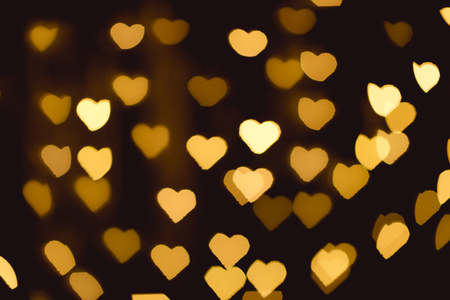 yellow heart shaped bokeh lights on black backdrop Foto de archivo