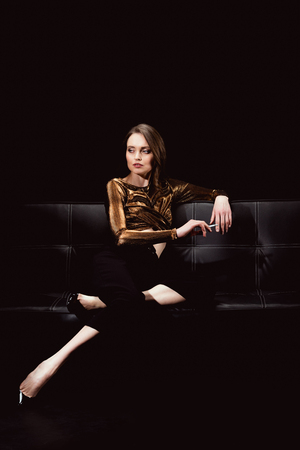 beautiful glamorous woman sitting on couch and smoking cigarette isolated on black Фото со стока