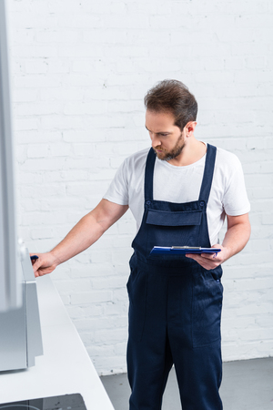 focused adult handyman with clipboard checking microwave oven in kitchen Imagens