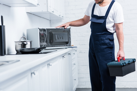 cropped shot of handyman with toolbox checking microwave oven in kitchen Imagens