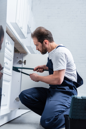 focused repairman in working overall fixing sink with pair of nippers in kitchen Stock Photo