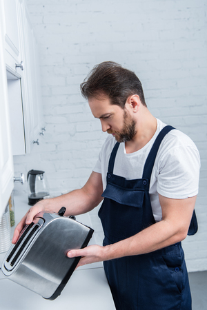 bearded craftsman in working overall fixing toaster in kitchen Stockfoto