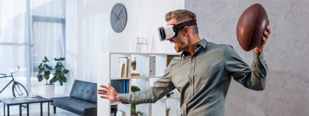 Panoramaaufnahme eines aufgeregten Geschäftsmannes, der ein Virtual-Reality-Headset trägt und American Football hält
