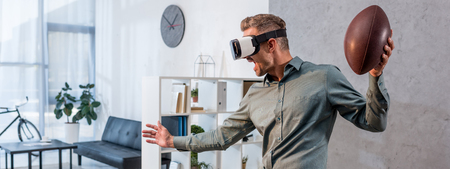 panoramic shot of excited businessman wearing virtual reality headset and holding american football Imagens