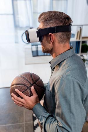 businessman wearing virtual reality headset and holding basketball