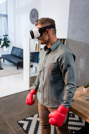 businessman wearing virtual reality headset and standing in boxing gloves in office Stock Photo