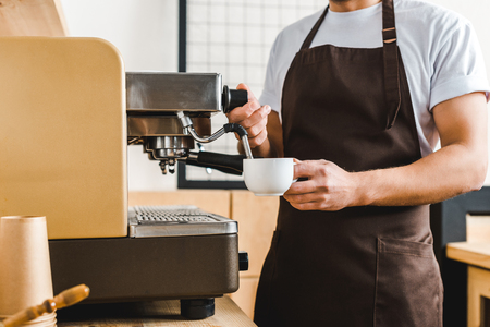 cropped view of handsome barista holding cup and making coffee with machine in coffee house Imagens