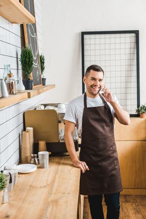 handsome cashier in brown apron talking on smartphone near coffee machine and bar counter in coffee house Banque d'images - 118432062