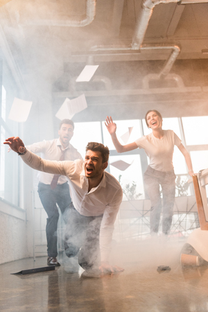 terrified businessman falling on floor while running and yelling near coworkers in office with smoke