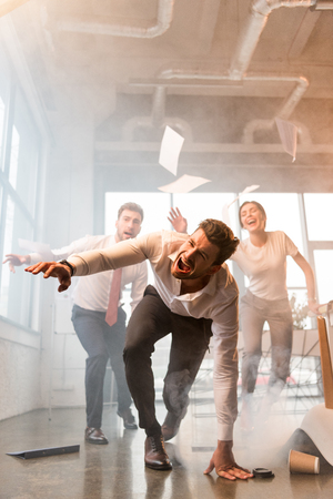 terrified businessman falling on floor while running and screaming near coworkers in office with smoke