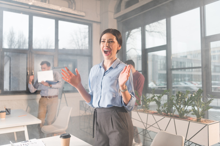 attractive businesswoman standing and screaming near coworkers in office with smoke Stok Fotoğraf