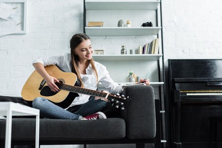 smiling girl sitting on couch with guitar, writing in notebook and composing music in living room