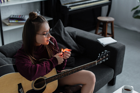 beautiful girl sitting, lighting marijuana joint and holding guitar at home