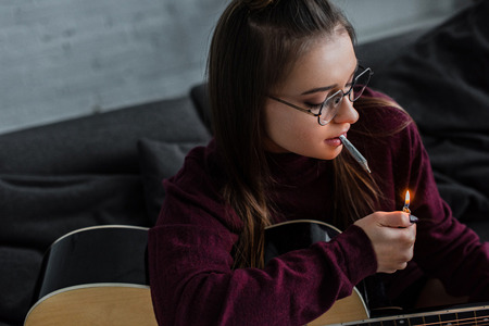 girl in glasses sitting, lighting marijuana joint and holding guitar at home Stock Photo