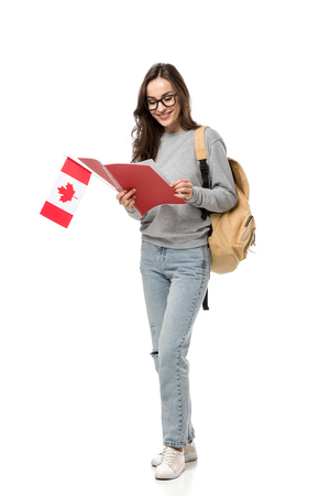female student in glasses holding canadian flag and looking at notebook isolated on white