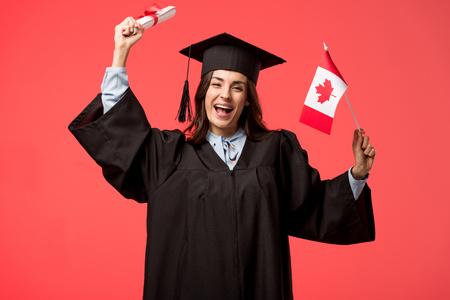 étudiante en robe universitaire tenant un drapeau canadien et un diplôme isolé sur du corail vivant Banque d'images