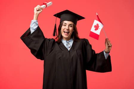 female student in academic gown holding canadian flag and diploma isolated on living coral Фото со стока