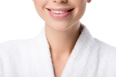 cropped view of smiling woman in bathrobe isolated on white