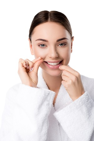 woman in white bathrobe flossing teeth and looking at camera isolated on white Stock Photo