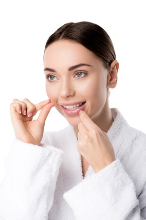beautiful woman in white bathrobe flossing teeth isolated on white Stock Photo