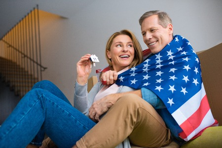 happy woman holding keys with house model trinket while wrapping in usa national flag with husband Banco de Imagens