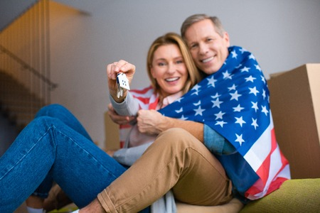 selective focus of woman holding keys with house model trinket while wrapping in usa national flag with husband
