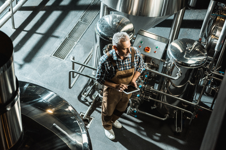 overhead view of brewer in working overalls using digital tablet in brewery Stok Fotoğraf