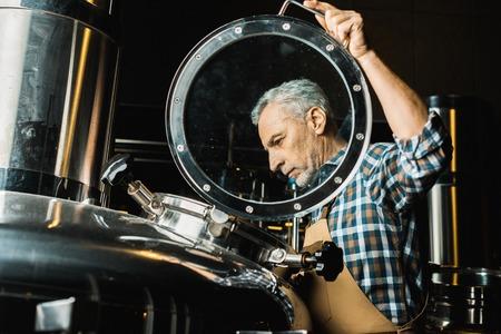 professioneller männlicher Brauer in Arbeitsoveralls, der die Brauereiausrüstung überprüft