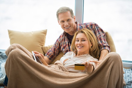 selective focus of woman showing credit card and holding digital tablet while resting with husband under soft fleece blanket