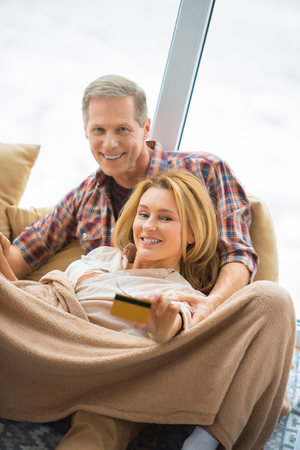 selective focus of pretty woman showing credit card while resting with husband by large window