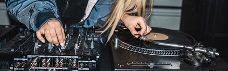 panoramic shot of dj woman standing near dj mixer and vinyl record Stok Fotoğraf