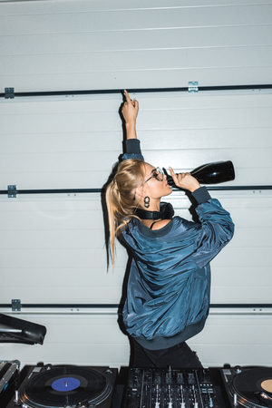 dj woman gesturing near dj mixer and drinking wine from bottle Imagens