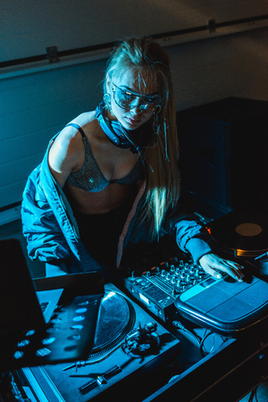 concentrated dj woman in glasses standing near dj mixer Reklamní fotografie