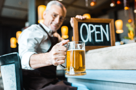 selective focus of senior owner of pub holding open sign and glass of beer