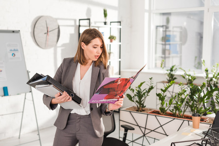 beautiful businesswoman holding folders and reading magazine while standing in office