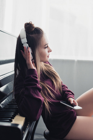attractive girl with headphones on head sitting on chair in front of piano and holding smartphone at home