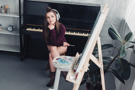 attractive girl with headphones on head sitting on chair in front of piano, holding smartphone and looking at easel in living room