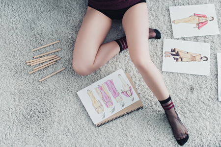 top view of cropped view of designer sitting on carpet near sketches and pencils