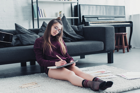 beautiful designer sitting on carpet near couch and drawing on notebook with pencil at home