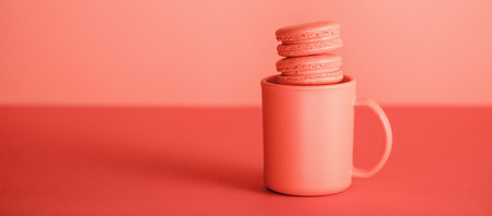 sweet macarons in cup on trendy Living coral background. Pantone color of the year 2019 concept 写真素材 - 118430802