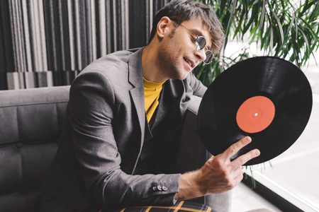 cheerful young man in sunglasses looking at vinyl record