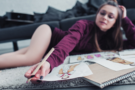 beautiful designer lying on carpet and holding pencil and sketch at home