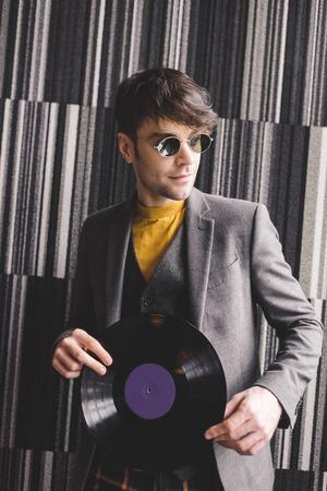 handsome young man in sunglasses holding plastic retro vinyl record Banco de Imagens