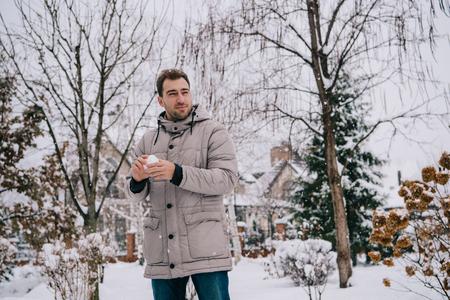 handsome man holding snowball in hands in winter Zdjęcie Seryjne - 118430891
